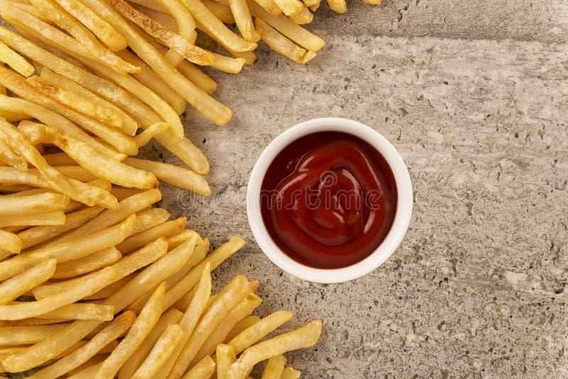 薯条和番茄酱碗在具体背景 库存图片