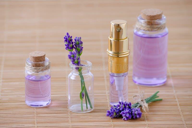 薰衣草香水和油在玻璃瓶和新鲜的淡紫色花在木背景 库存照片