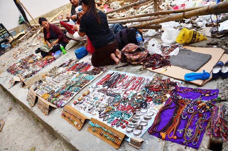 藏族为旅客卖纪念品在路旁边在博克拉 免版税库存图片