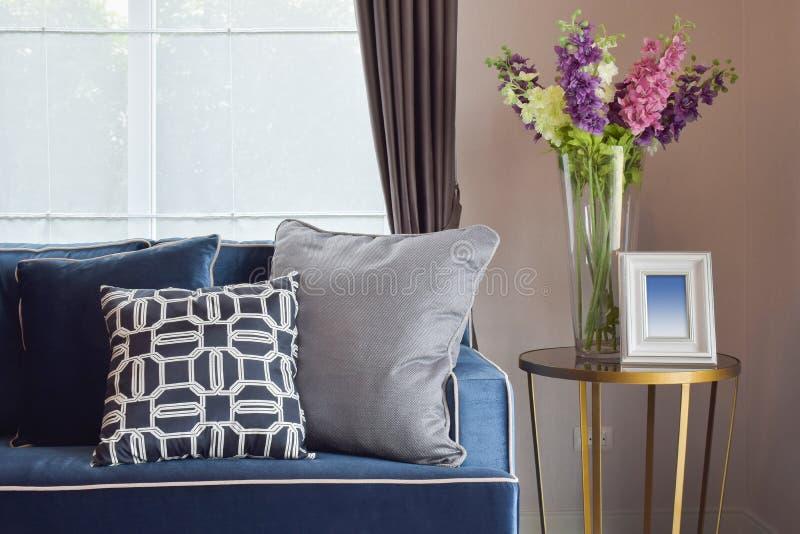 藏青色现代经典沙发和减速火箭,灰色和蓝色枕头有一个可爱的兰花花瓶的 免版税库存照片