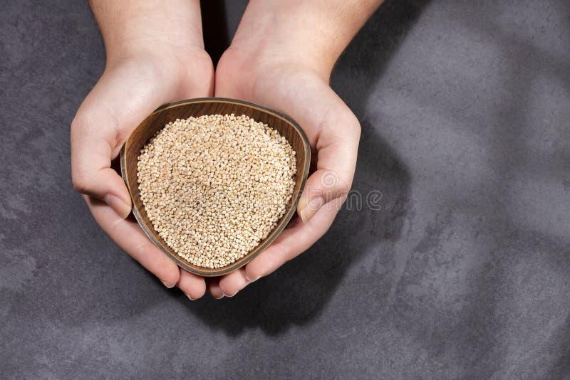 藜麦 — 女手握碗,白藜麦种子 免版税库存照片