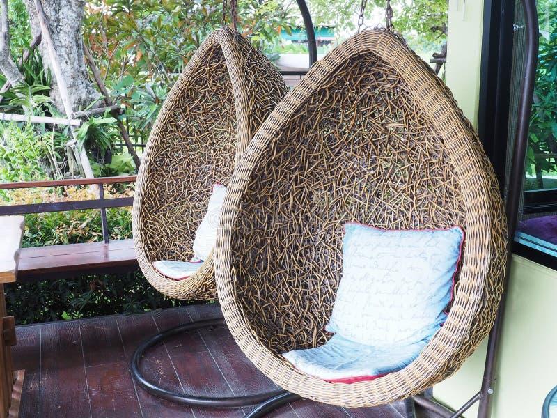 藤条休息室垂悬的椅子丝毫白色枕头 藤条休息室吊 免版税库存照片