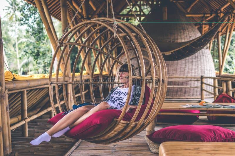 藤条休息室垂悬的椅子的少妇与在阳台的枕头有绿色自然热带背景 免版税库存照片