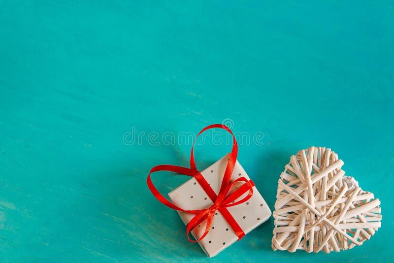 藤条被编织的白色装饰心脏典雅的礼物弓栓与在Painted绿松石背景华伦泰母亲` s的红色丝带弓 免版税库存照片