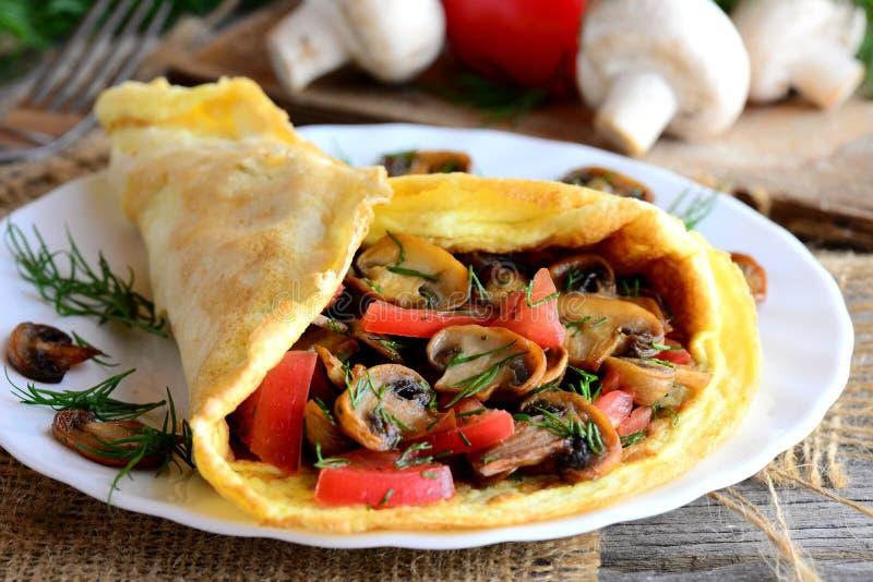蘑菇和蕃茄煎蛋卷想法 家庭煎蛋卷充塞用蘑菇、蕃茄和莳萝在板材和葡萄酒木桌 免版税库存图片