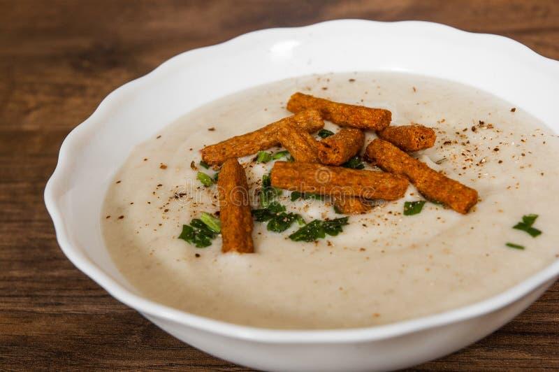 蘑菇奶油色汤用油煎方型小面包片、草本和香料 免版税库存图片