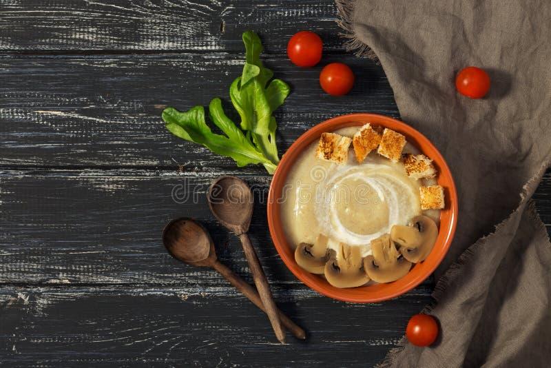 蘑菇汤纯汁浓汤用在土气背景的油煎方型小面包片与木匙子 库存照片