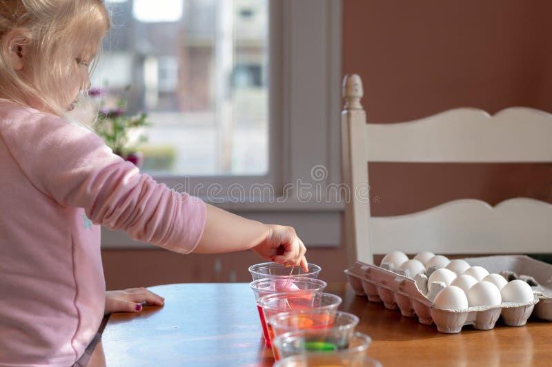 蘸在染料的少女鸡蛋复活节的 免版税库存照片