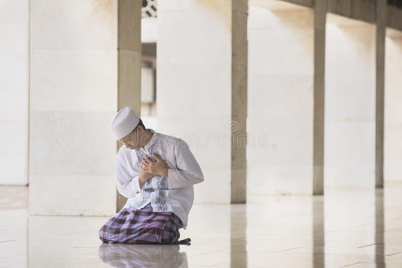 虔诚的回教人看起来哀伤在清真寺 库存照片