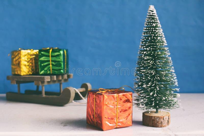 虚假圣诞树和礼物在一点雪橇 新年好和圣诞快乐概念 贺卡或欢乐背景 免版税图库摄影