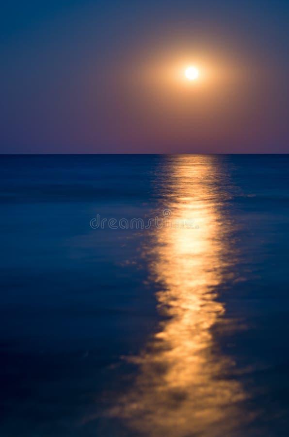 虚度在夜蓝天,海天线,波浪,光的反射 免版税库存图片