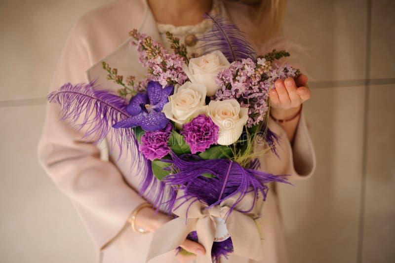 虹膜、玫瑰和丁香豪华的花束在紫色包裹 免版税库存照片