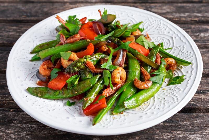 虾和芦笋混乱油煎在白色板材的食物 库存图片