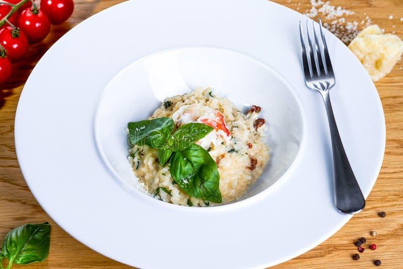 虾用在一块白色板材的米有在木背景的叉子的 与鸡、蘑菇和巴马干酪的意大利煨饭 免版税库存照片