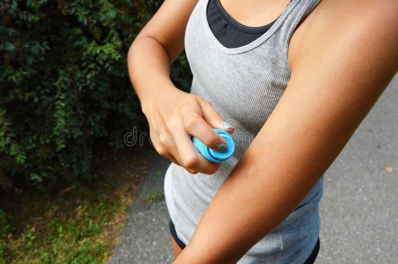 蚊子放水剂浪花 反对臭虫的妇女喷洒的杀虫剂在胳膊皮肤咬住室外在自然森林里使用浪花 库存图片
