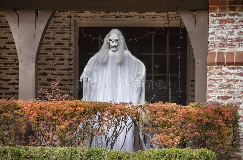 蛇神在门廊的鬼魂身分在秋天万圣节装饰的色的树篱后 免版税库存照片