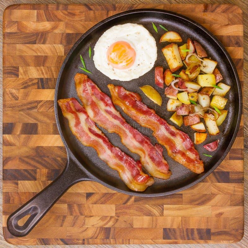 蛋和烟肉早餐的晴朗的边用土豆 图库摄影