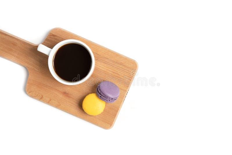 蛋白杏仁饼干和一杯咖啡在木板的 免版税库存图片