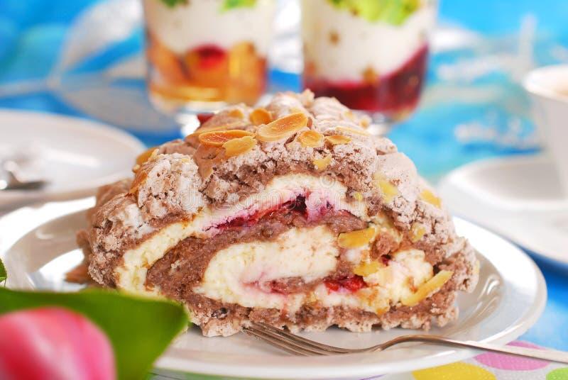 蛋白甜饼与樱桃奶油和杏仁的卷蛋糕蛋糕 库存图片