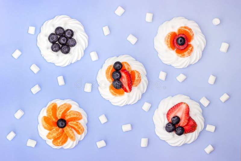 蛋白甜饼和蛋白软糖用莓果在淡紫色背景 r 免版税库存图片