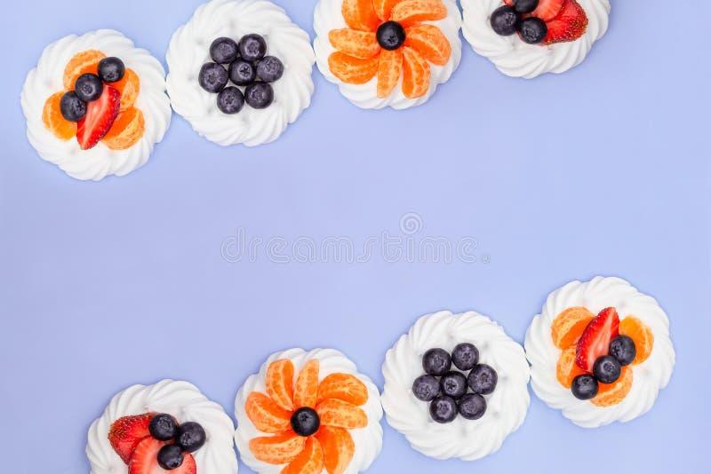 蛋白甜饼框架用蓝莓、草莓和蜜桔在淡紫色背景 r 免版税图库摄影