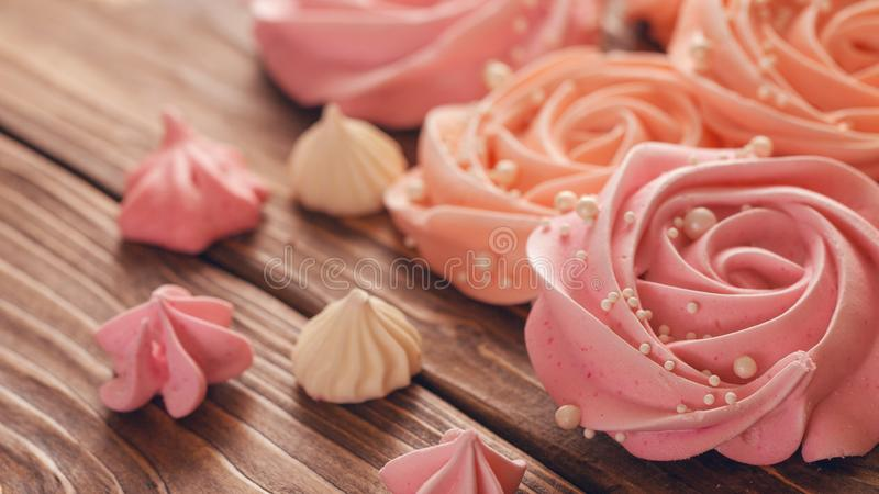 蛋白甜饼淡粉红以玫瑰或花的形式 蛋白甜饼是很多蛋糕装饰 免版税库存图片