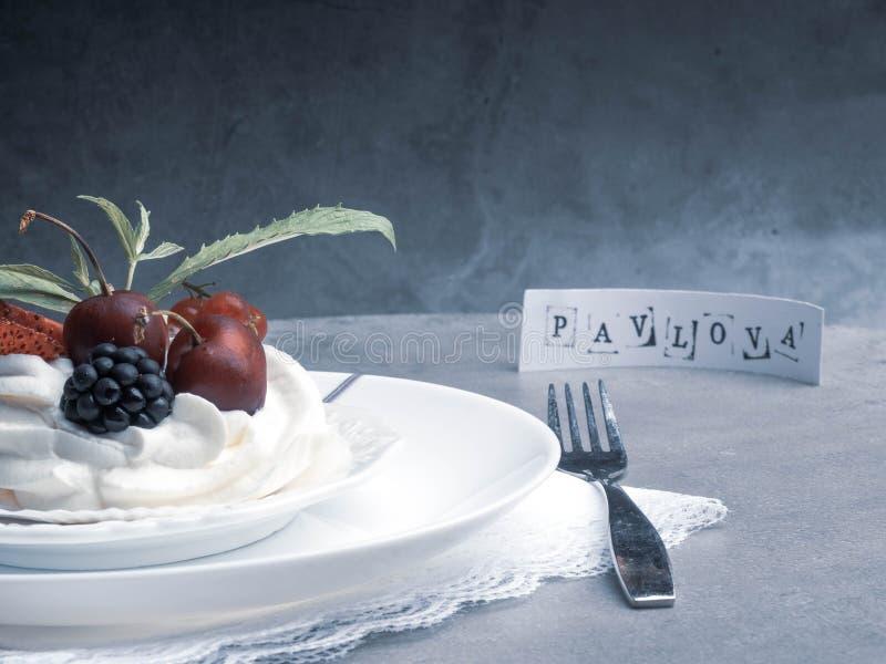 蛋白甜饼蛋糕帕夫洛娃片断与打好的奶油和新鲜的草莓,黑莓,樱桃,无核小葡萄干,薄菏的 库存照片