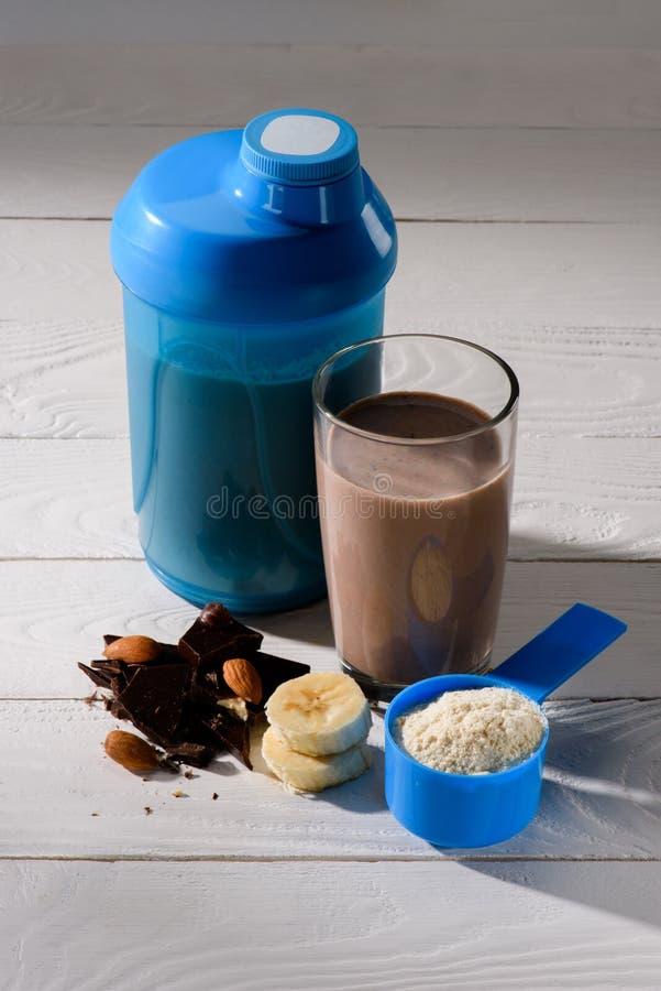 蛋白质震动振动器和玻璃用杏仁、香蕉和巧克力在白色 库存图片