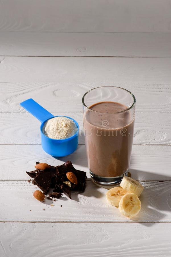 蛋白质震动玻璃用杏仁、香蕉和巧克力在白色 免版税库存图片
