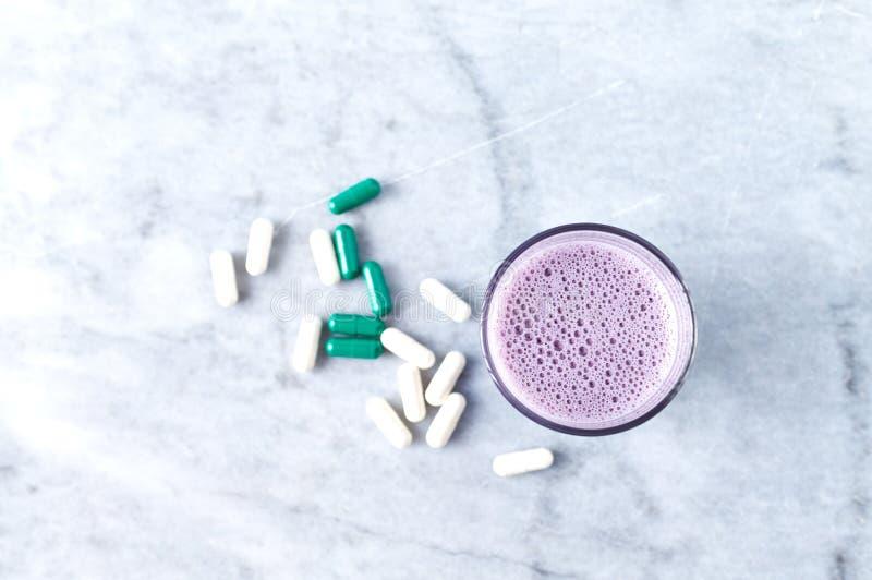 蛋白质震动玻璃用牛奶和蓝莓、Beta胺基代丙酸和L肉毒碱胶囊在背景中 体育建身的nutriti 免版税图库摄影