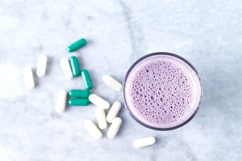 蛋白质震动玻璃用牛奶和蓝莓、Beta胺基代丙酸和L肉毒碱胶囊在背景中 体育建身的nutriti 库存图片