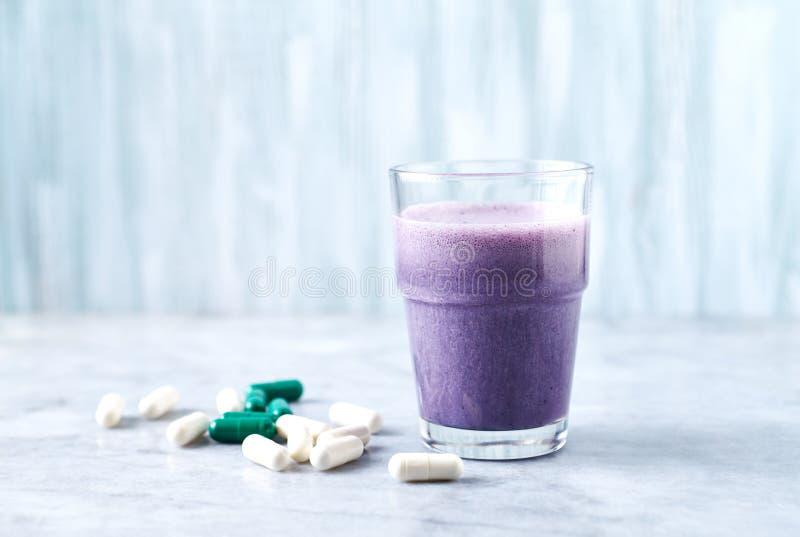 蛋白质震动玻璃用牛奶和蓝莓、Beta胺基代丙酸和L肉毒碱胶囊在背景中 体育建身的nutriti 库存照片