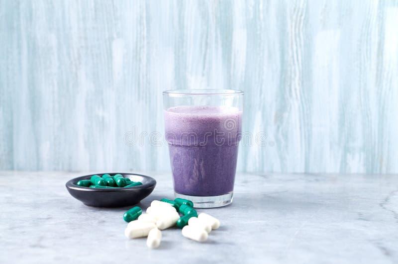蛋白质震动玻璃用牛奶和蓝莓、Beta胺基代丙酸和L肉毒碱胶囊在背景中 体育建身的nutriti 免版税库存图片