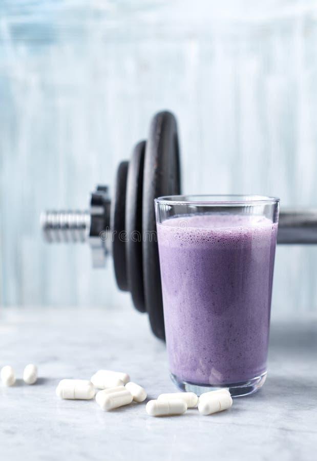 蛋白质震动玻璃用牛奶和蓝莓、Beta胺基代丙酸胶囊和一个哑铃在背景中 体育建身的nutritio 免版税图库摄影