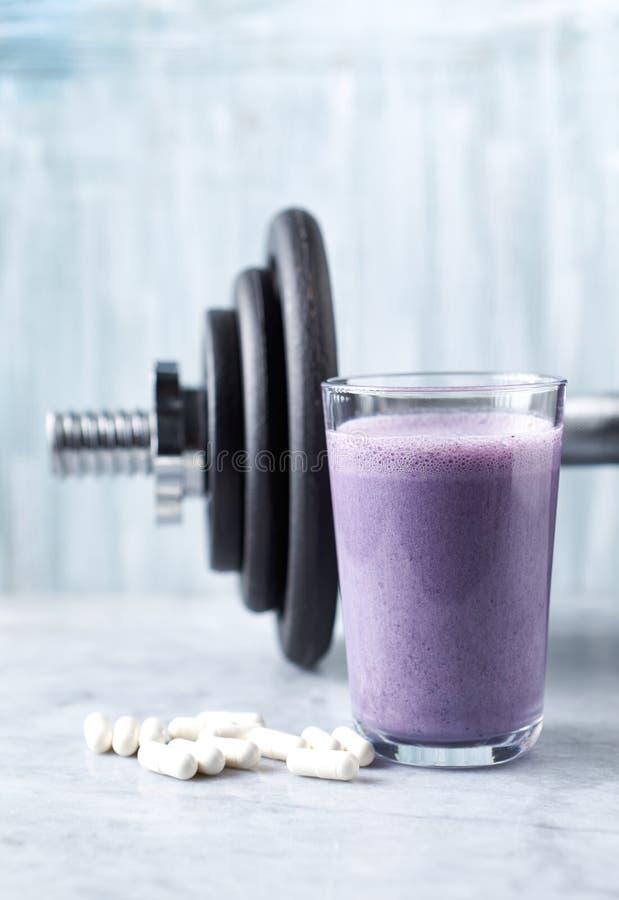 蛋白质震动玻璃用牛奶和蓝莓、Beta胺基代丙酸胶囊和一个哑铃在背景中 体育建身的nutritio 免版税库存照片