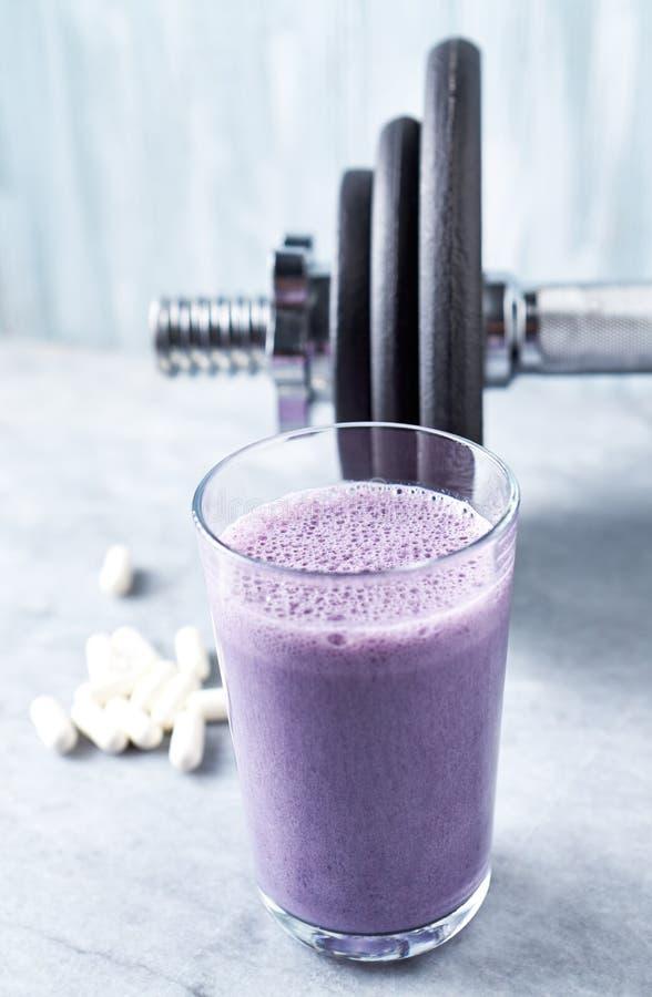 蛋白质震动玻璃用牛奶和蓝莓、Beta胺基代丙酸胶囊和一个哑铃在背景中 体育建身的nutritio 免版税库存图片