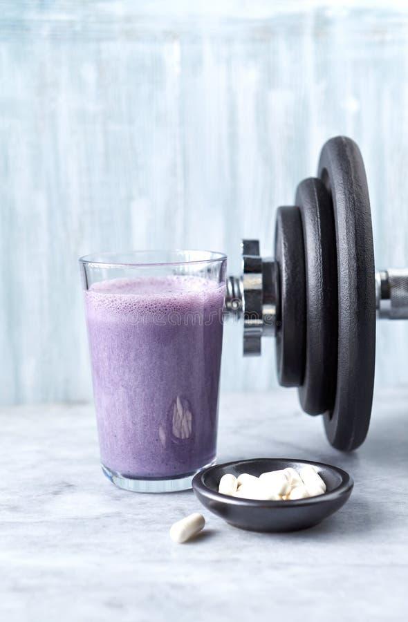 蛋白质震动玻璃用牛奶和蓝莓、Beta胺基代丙酸胶囊和一个哑铃在背景中 体育建身的nutritio 库存图片