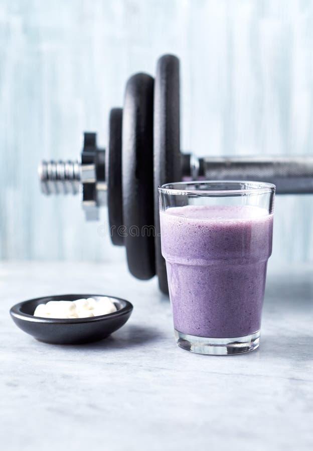 蛋白质震动玻璃用牛奶和蓝莓、Beta胺基代丙酸胶囊和一个哑铃在背景中 体育建身的nutritio 库存照片