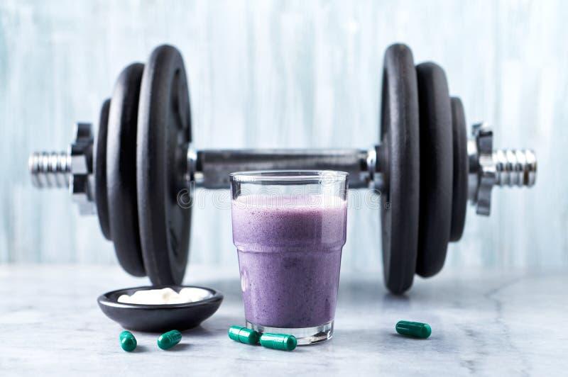 蛋白质震动玻璃用牛奶和蓝莓、L肉毒碱胶囊和一个哑铃在背景中 体育建身的营养 免版税库存图片