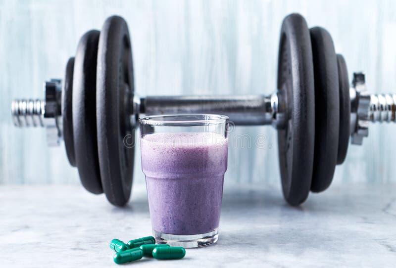 蛋白质震动玻璃用牛奶和蓝莓、L肉毒碱胶囊和一个哑铃在背景中 体育建身的营养 库存照片