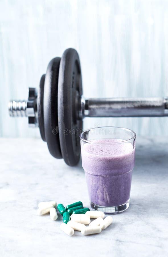 蛋白质震动玻璃用牛奶和蓝莓、L肉毒碱胶囊和一个哑铃在背景中 体育建身的营养 库存图片