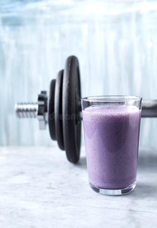 蛋白质震动用牛奶和蓝莓和一个哑铃玻璃在背景中 体育建身的营养 库存照片
