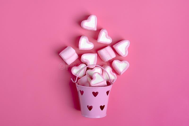 蛋白软糖和心形的糖果从一桃红色铁bucketon溢出桃红色背景情人节快乐 免版税图库摄影