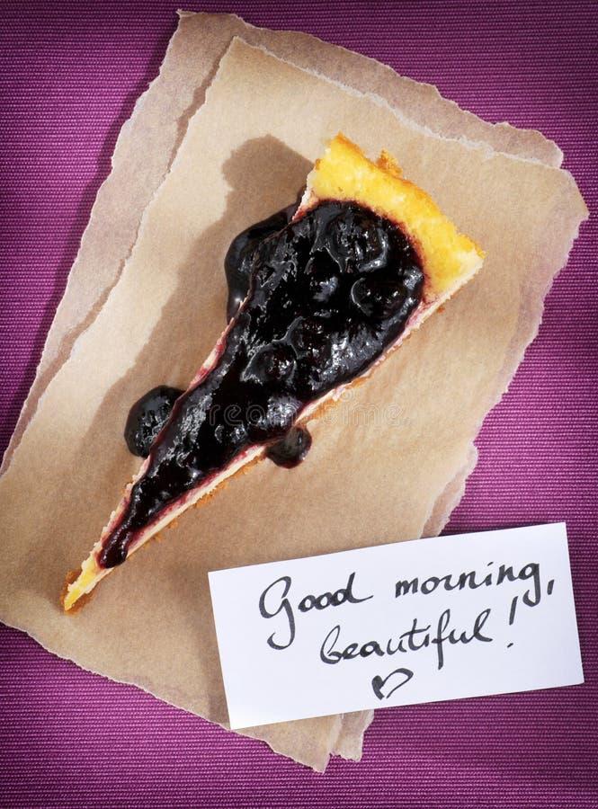 蛋糕和早晨好消息在紫色背景从上面 免版税库存图片