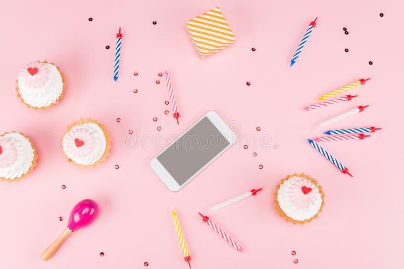 蛋糕和智能手机顶视图与蜡烛的有装豆子小布袋大模型的 免版税库存照片