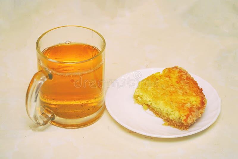 蛋糕在一杯茶碟和茶的 免版税图库摄影