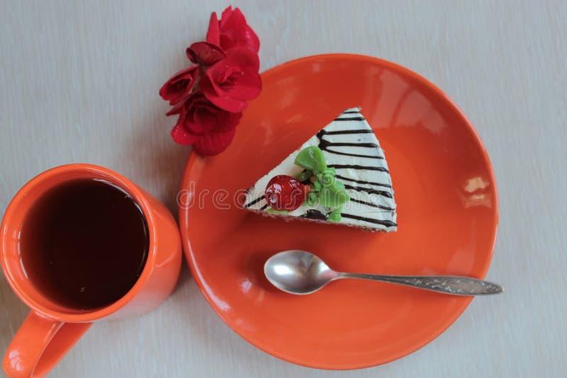 蛋糕在橙色盘和茶的 免版税库存图片