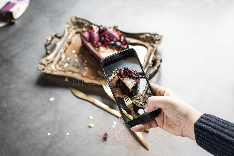 蛋糕在金盘子的通过手机屏幕被拍摄 电话在有美好的修指甲的一只女性手上 免版税库存照片
