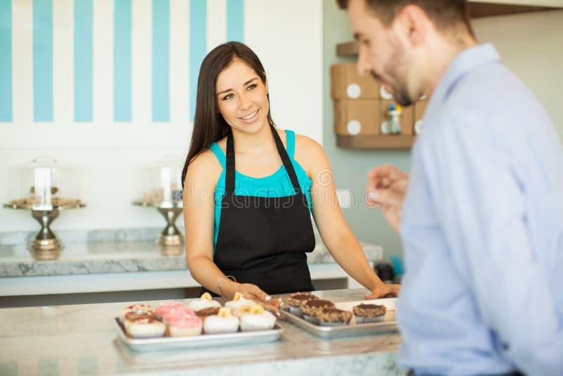 Download 蛋糕显示杯形蛋糕的商店雇员 库存照片. 图片 包括有 烘烤, 女性, 舒适, 讲西班牙语的美国人, 逗人喜爱 - 59109856
