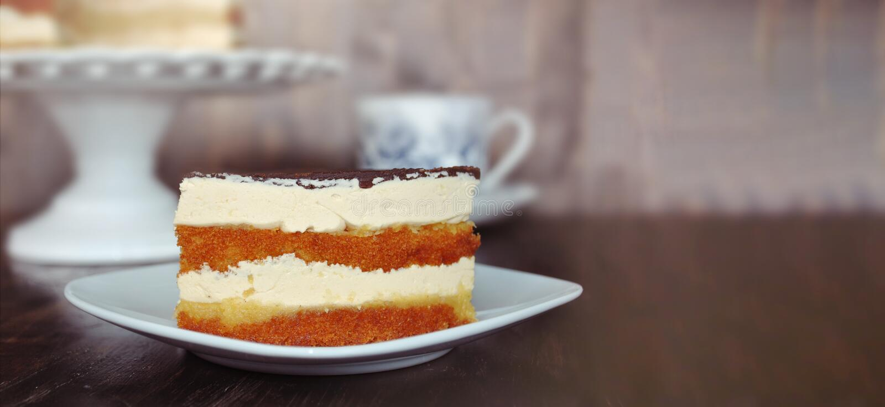 蛋糕立即可食服务与A杯子COFFE或茶反对木桌 库存照片